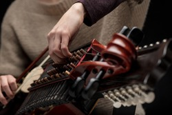 Woman musician adjusting the tangents of her nyckelharpa in a close up on her hands as she prepares for a live performance or rehearsal