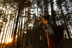 Woman naturalist in hat and orange overalls with backpack looking at the sun through her fingers at sunset, exploring wildlife and ecotourism adventure walking in a wildlife national park.