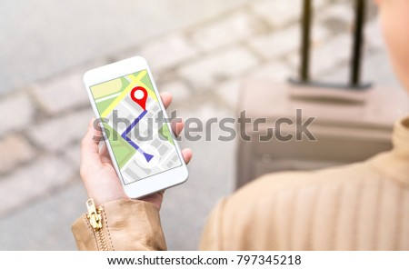 Woman navigating with mobile phone map application. Tourist with walking route on smartphone screen. Traveler with baggage using GPS to find destination or hotel on vacation.