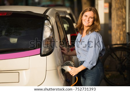Woman near a rental electric car. Vehicle charged at the charging station. #752731393