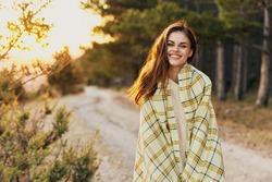 woman near coniferous forest road plaid sunset