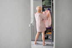 Woman near wardrobe for cloths with clothes on a hanger. Girl trying clothing. Closet with bags, boxes and shoes. Stock photo