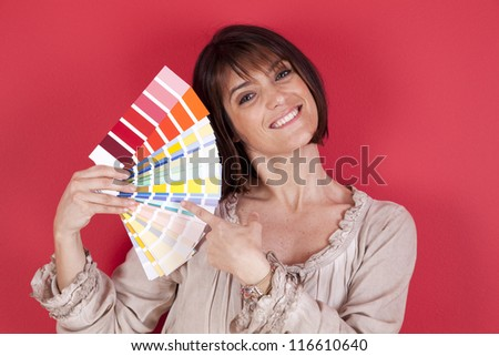 woman next to a red wall looking to a color paint palette (selective focus) - stock photo