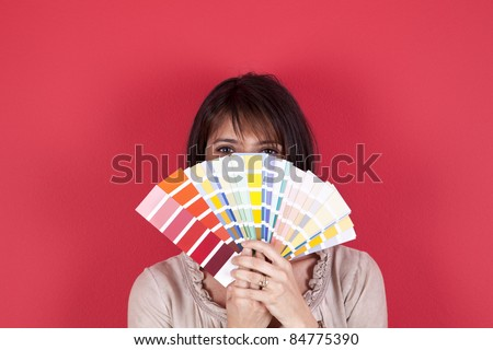 woman next to a red wall looking to a color paint palette (selective focus)