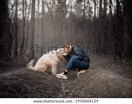 woman of forty years with a dog in a gray dark forest in early spring Stock photo ©