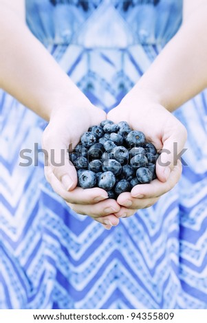 Woman offers freshly picked blueberries. Shallow depth of field. - stock photo