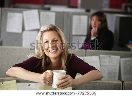Woman office worker enjoys a cup of coffee at her cubicle - stock photo