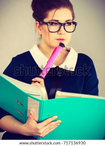 Woman office worker holding blue file folder and big pink pen in hands. Businesswoman or secretary wearing nerdy glasses with documents bills. Thinking face expression. Business and paperwork on grey