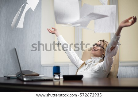 Woman office worker throws the paper at workplace. Beautiful  female office worker sits in a chair at his desk with his hands raised upward and outward throwing paper. The end of the working week Сток-фото ©