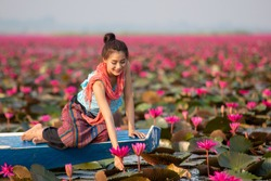 Woman on a boat in the lake red Lotus,Beautiful women in Lotus Gardens.