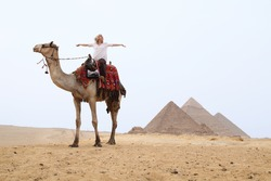 woman on a camel in the desert in front of the pyramids in egypt
