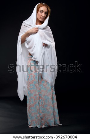 Woman on a dark background in a white robe. Woman in a white cloak