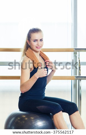 Woman on a fitness ball in  gym #375562117