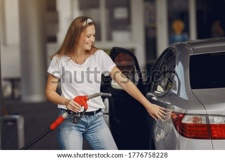 Woman on a gas station. Lady in a white t-shirt. Woman near the car. Сток-фото ©