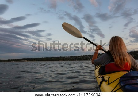 Woman on a kayak is paddling in the ocean during a vibrant sunset. Taken in Vancouver, British Columbia, Canada. #1117560941