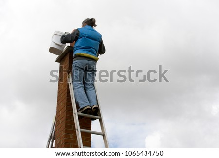 Woman on a ladder cleaning a brick chimney
