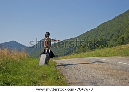 Woman on a mountain road making of hitch-hiking