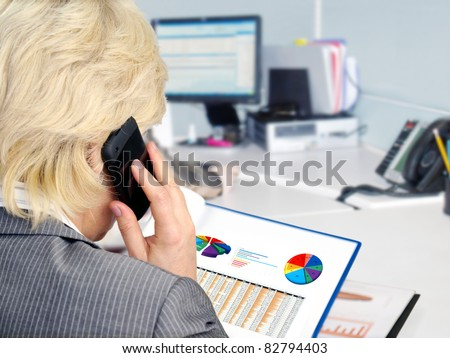 Woman on a phone analyzing financial data and charts .