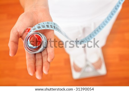 Woman on a scale with a measuring tape