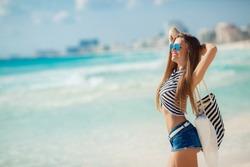 Woman on a tropical beach with beach bag. fit young woman with stripy bag at tropical beach. beautiful girl walking the summer beach