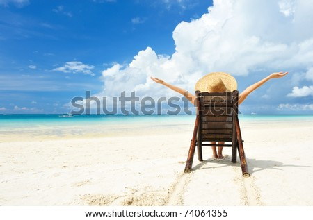Woman on a tropical beach with hat