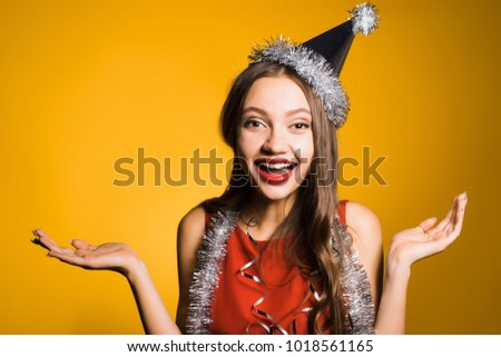 woman on a yellow background having fun at a New Year party #1018561165