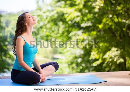 Woman on a yoga mat to relax outdoor.