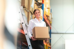 Woman on an ladder in stock with box