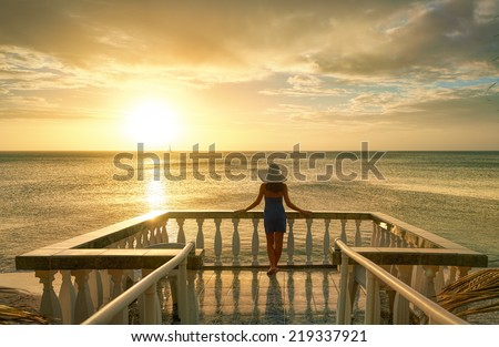 Woman on balcony looking at the beautiful sunset