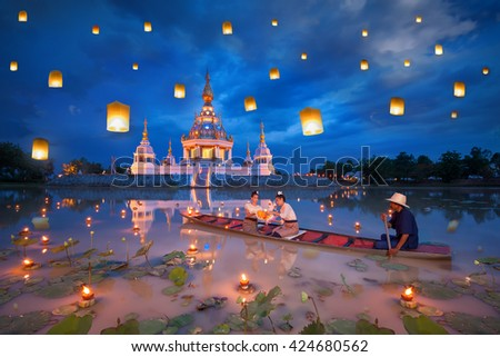 Woman on boat for kratong and floating lamp festival in pagoda background