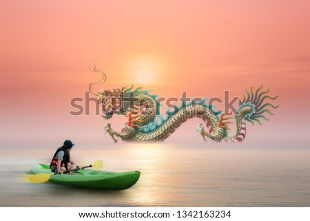 Woman on boat look at Chinese Dragon statue in the sea with sunset background. Surreal concept