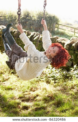 Woman on country garden swing