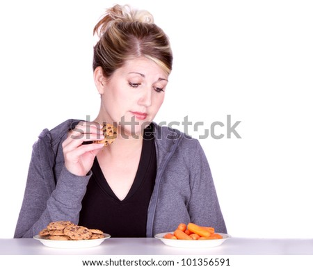 Woman on diet making eating choices, choosing between carrots or cookies. - stock photo