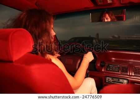 Woman on drivers seat, focus on mirror