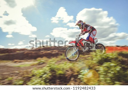 woman on enduro motocross in motion, desire for victory, dynamics of speed. #1192482433