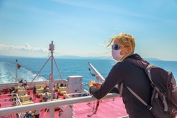 Woman on ferry boat with a surgical mask during Covid-19 looking Tuscany panorama. Tourist travels on Tyrrhenian Sea to Elba Island by ferry. Coronavirus quarantine holiday travel in Italy with COVID.