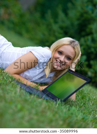 woman on grass with recycle logo on laptop screen