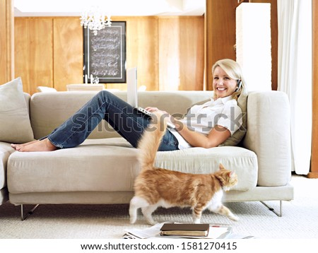 Woman on home sofa with telephone headset working on laptop with cat and smiling at camera