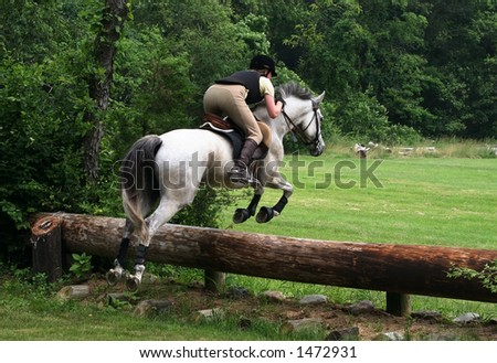 woman on horse jumping - stock photo