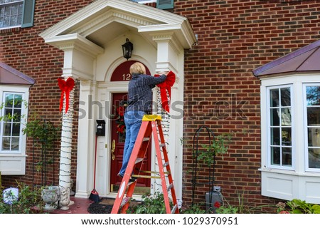 Woman on ladder putting Christmas decorations up on pillars of entrance of two story brick house with bay windows #1029370951