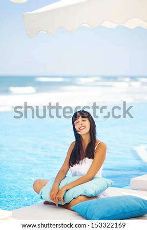 woman on lounger near swimming pool