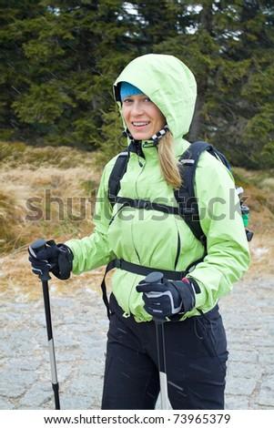 Woman on nordic walking trip in winter mountains