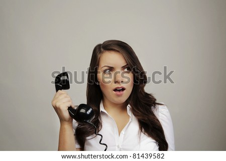 woman on old BT telephone looking surprised