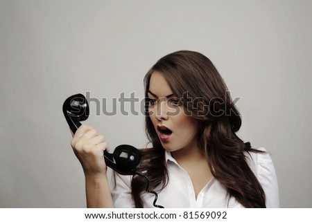 woman on old telephone looking surprised