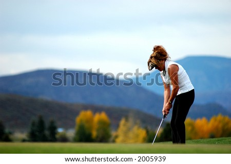 woman on putting green in white sleeveless blouse and black pants making shot