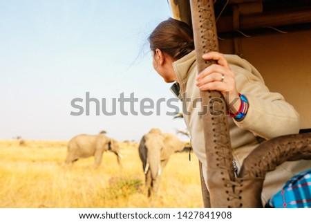 Woman on safari game drive enjoying close encounter with elephants in Kenya Africa