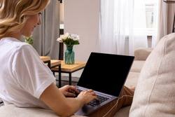 Woman on sofa working on laptop with mockup blank screen. Empty copy space on monitor for advertisement. Black screen.