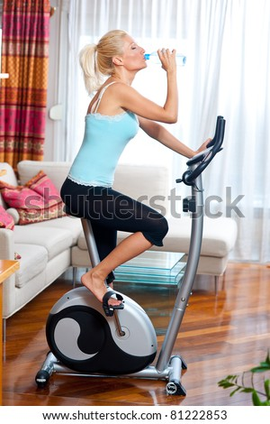 woman on stationary bicycle with water bottle in her home relaxing