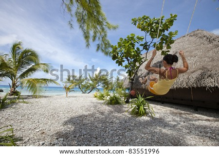 Woman on swing front of blue lagoon in a paradise beach near bungalow