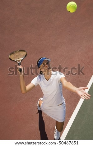 Woman on tennis court Serving Tennis Ball, elevated view